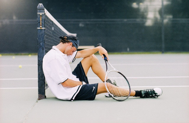 Tired Tennis Player Sitting on Court