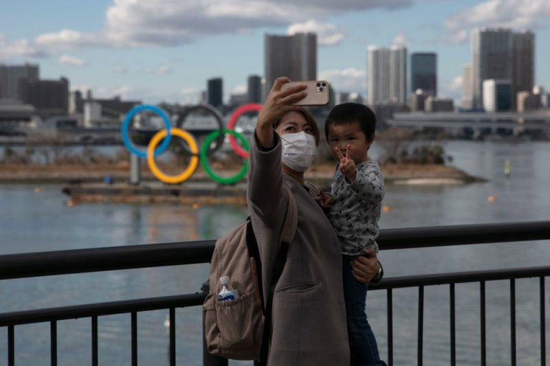 Woman and child posing for selfie in front of 2020 Tokyo Olympics logo